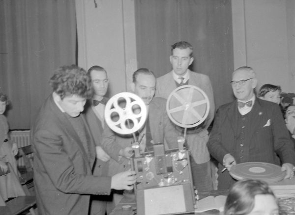 Film society members operating a film projector