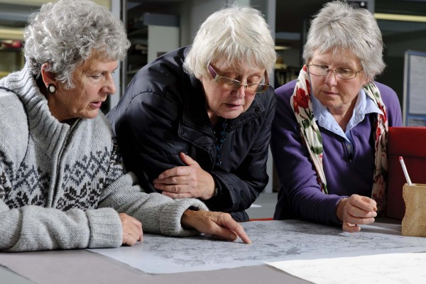 Three women looking at a map in the archive reading room