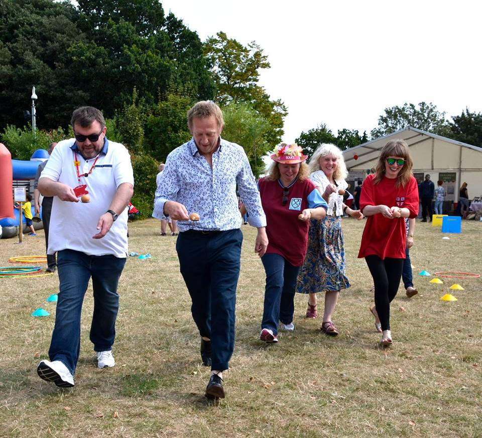 Adults taking part in the egg and spoon race